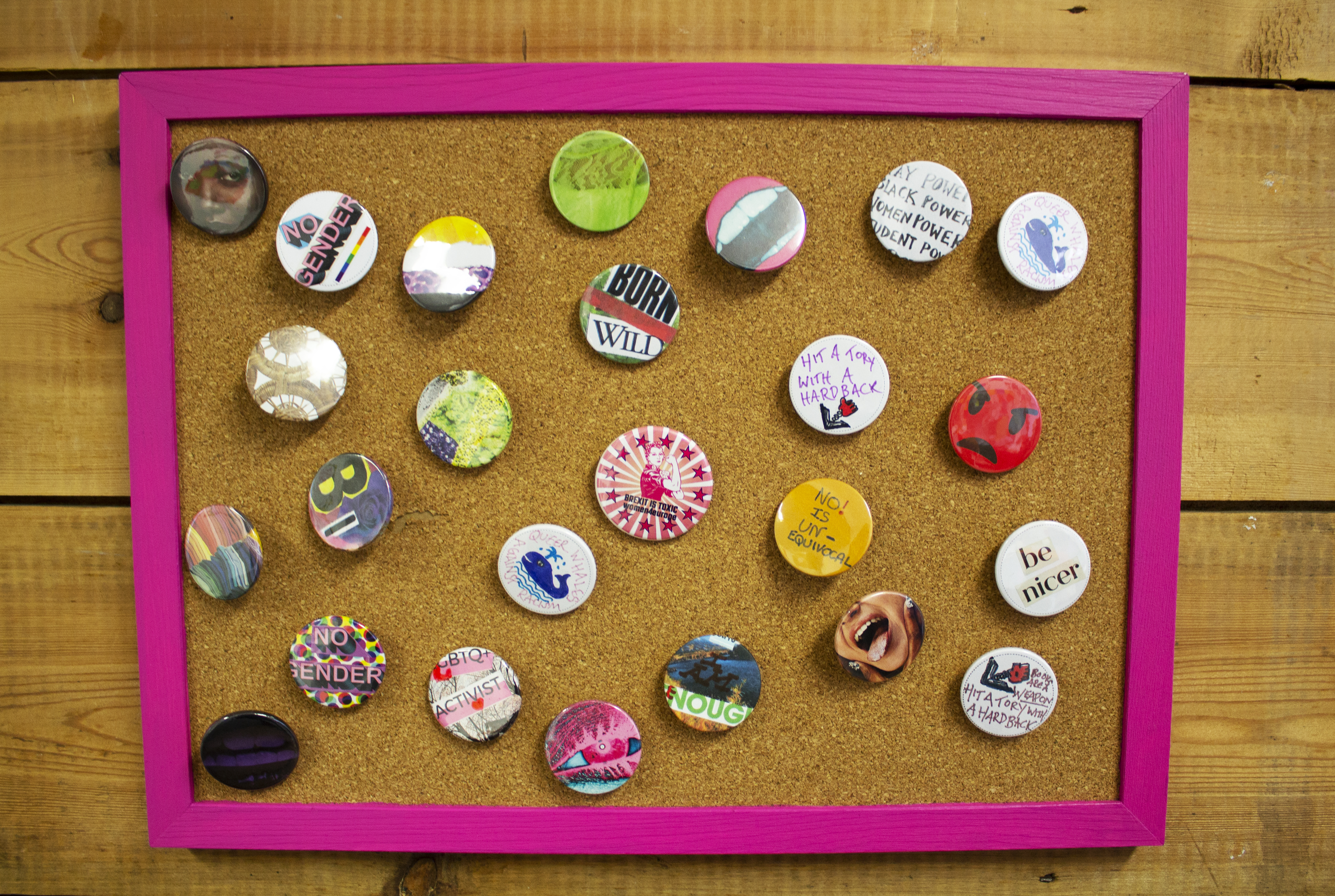 close up of badges displayed on exhibition wall, some badges say 'be nicer', 'bi', 'no gender'