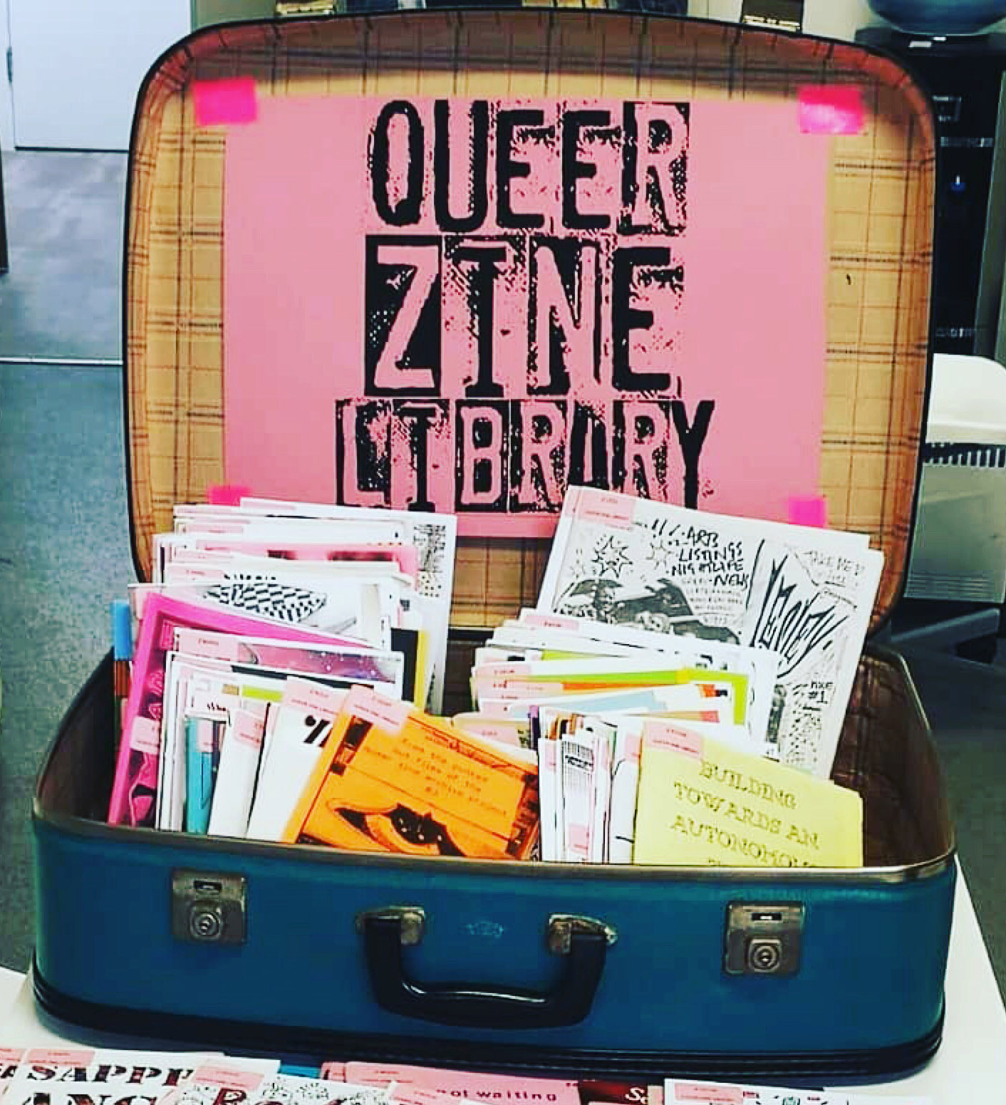 open suitcase full of zines, with a a sign saying 'queer zine library'